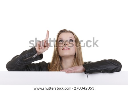Teenage girl leans across a white wall isolated