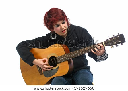 Teenage girl learning to play guitar