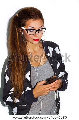 Teenage girl listening music on mobile on white background.Young beautiful hipster woman listening music with headphones.Close up fashion lifestyle summer image of sexy woman with amazing smile. - stock photo
