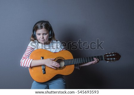 Teenage girl listening to music on headphone wearing white and red top and playing guitar sitting on a stool with a grey background