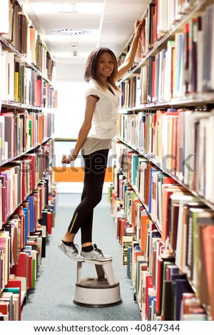 Teenage girl looking for a book in the library - stock photo
