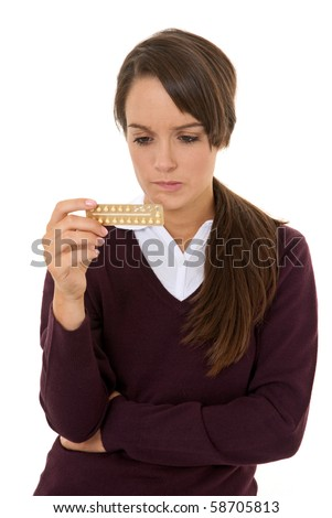 Teenage girl looking worried at contraception pills isolated on white - stock photo