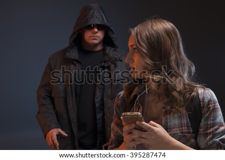 Teenage girl looks over her shoulder because she feels someone is about to attack her. Scary man grabs a girl on her phone.   - stock photo