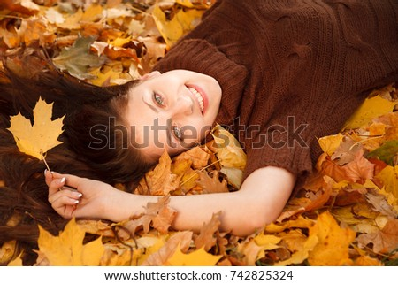 teenage girl lying down on yellow maple leaves smiling looking at camera