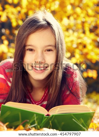 teenage girl lying on fallen leaves in the park and reading a book. learning and education in autumn