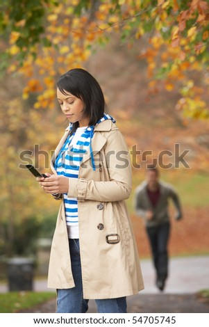 Teenage Girl Making Mobile Phone Call With Boyfriend Running Towards Her In Background - stock photo