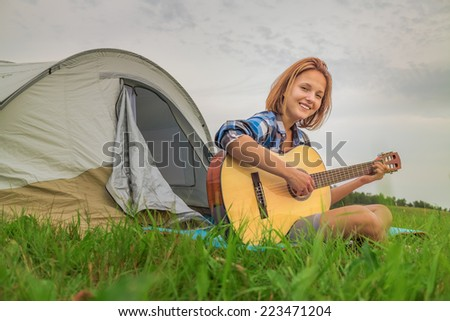 Teenage  girl near the tent playing a guitar while sitting on a green grass - stock photo