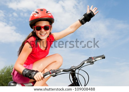 teenage girl on a bicycle with hand up - stock photo