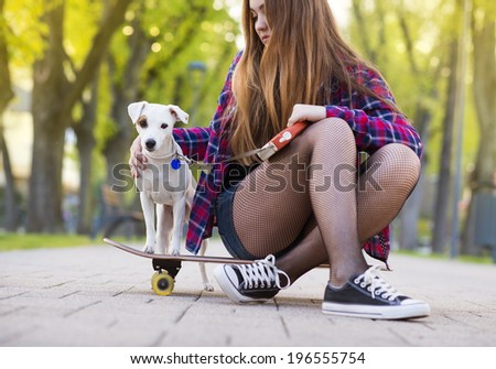 Teenage girl on skateboard with her dog - stock photo