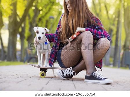 Teenage girl on skateboard with her dog - stock photo