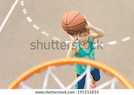 Teenage girl playing basketball taking aim at the goal with the ball raised in her hands, view from on top of the goalpost and net - stock photo