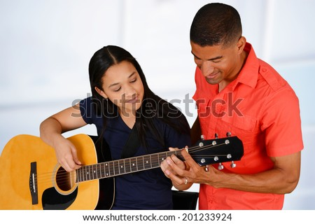 Teenage girl playing the guitar on a white background