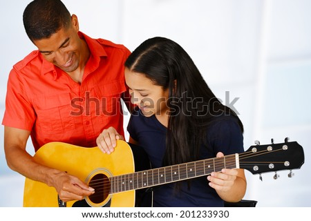 Teenage girl playing the guitar on a white background - stock photo