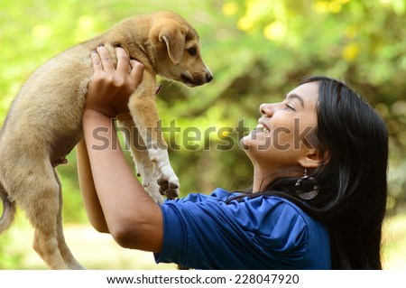 Teenage girl playing with puppy dog - stock photo
