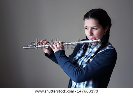 Teenage girl plays the flute. - stock photo