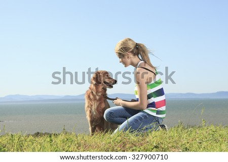 Teenage girl plays with the dog outside. The dog give his foot. - stock photo