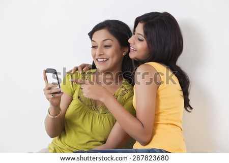 Teenage girl pointing on mobile phone - stock photo