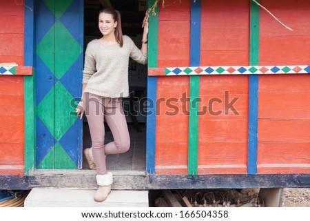 Teenage girl posing at the door of colorful storeroom - stock photo