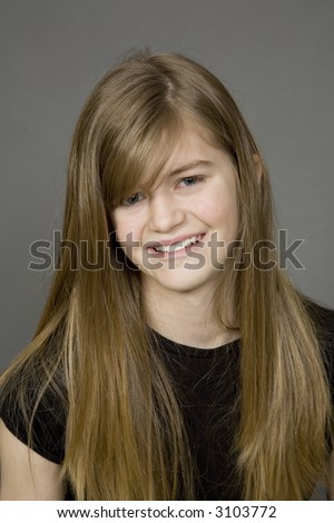 Teenage girl posing on a gray background with a smile