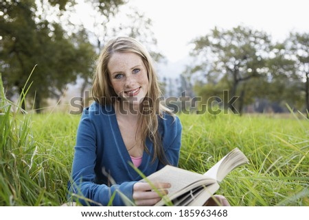 Teenage girl reading book in field