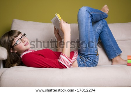 Teenage girl relaxing with book on a sofa.
