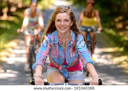 Teenage girl riding bike with friends on countryside road - stock photo