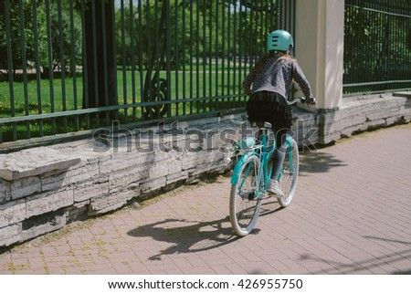 Teenage girl riding in a street with a bicycle  - stock photo