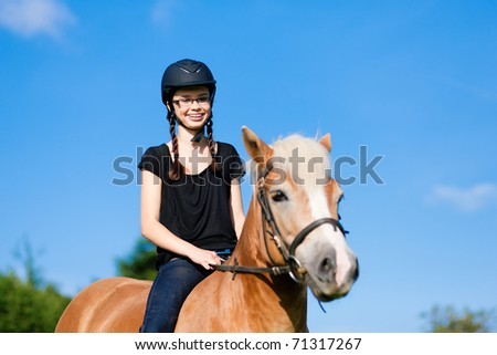 Teenage girl riding in summer with her horse - stock photo