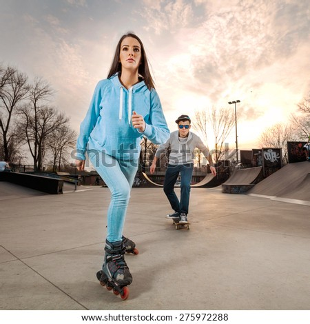 Teenage girl rollerblading in a skate park with a boy skateboarding in the background - stock photo