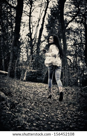 Teenage girl running scared away from camera in woods - stock photoGirl Running Away From Boy