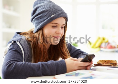 Teenage Girl Sending Text Message Whilst Studying - stock photo