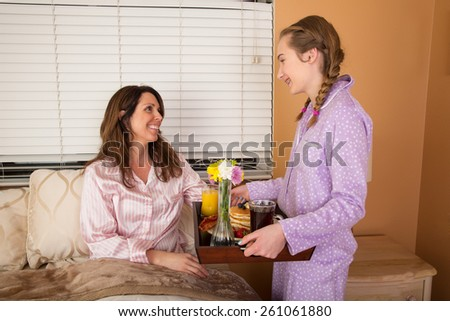 Teenage girl serving her Mom breakfast in bed on Mothers Day - stock photo