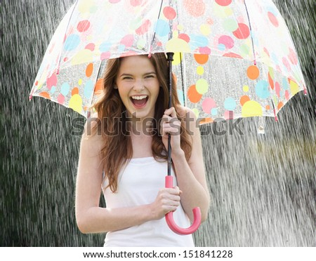 Teenage Girl Sheltering From Rain Beneath Umbrella - stock photo