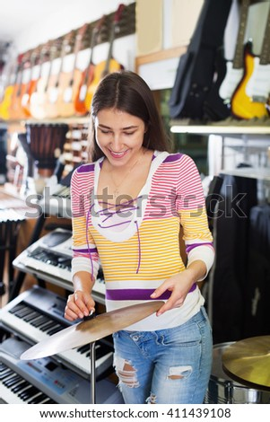 Teenage girl shopping drum kit in music instruments studio