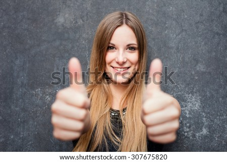Teenage girl showing thumbs up with both hands - stock photo