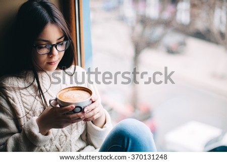 Teenage girl sitting at a window and holding a cup of coffee on a cold autumn day - stock photo