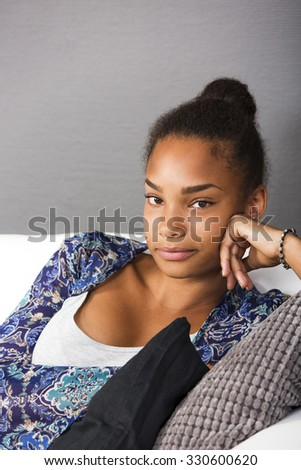 Teenage girl sitting in a couch looking into camera with a friendly smile - stock photo