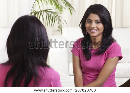 Teenage girl sitting in front of mirror - stock photo
