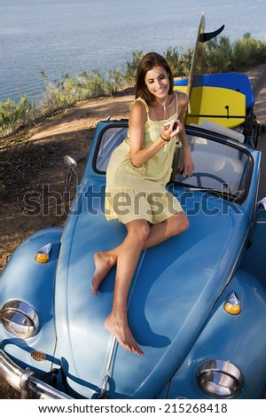 Teenage girl sitting on car bonnet, listening to MP3 player, smiling, elevated view