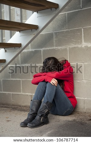 Teenage girl sitting under staircase in alley-way in a depressed state.