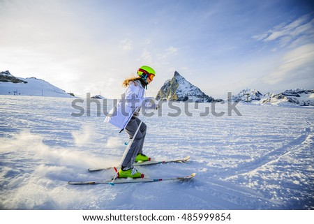 Teenage girl skiing in Swiss Alps in Sunny Day, Matterhorn in Background