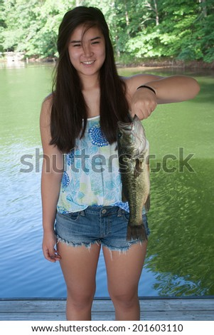 Teenage girl smiling and holding a largemouth bass - stock photo