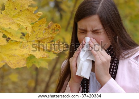 teenage girl sneeze into handkerchief with maple leaf in foreground - stock photo