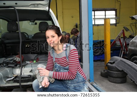 Teenage girl standing by vehicle in workshop - stock photo