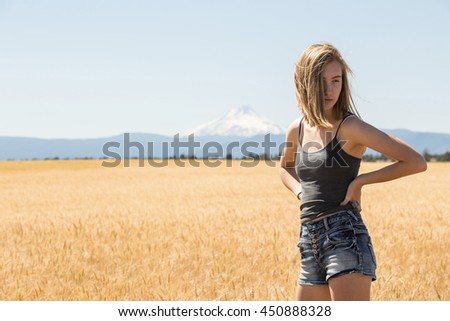 Teenage girl standing in a wheat field - stock photo