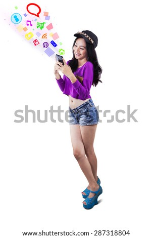 Teenage girl standing in the studio while using social media on her smartphone, isolated on white - stock photo