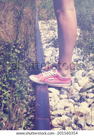 Teenage girl standing on the railway tracks on a hot summer day, retro style - stock photo