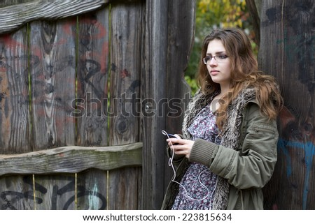 teenage girl standing outside and holding her phone - stock photo