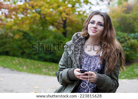 teenage girl standing outside and looking at her phone - stock photo