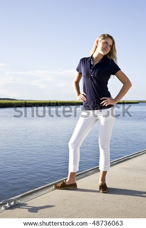 Teenage girl standing posed on dock by water on sunny day - stock photo